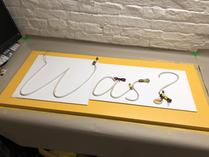 Using the foam board cutouts to position the letters on the base plate. Note the very tightly bent strip for the question-mark-dot.